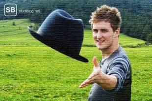 Student der auf einer Wiese stehend seinen Hut wift - zum Thema Begriffe im Studium
