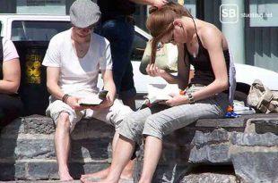 Bücherwürmer die auf einer Mauer in der Sonne sitzen und lesen