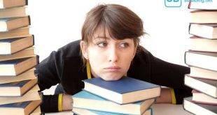 Zeitmanagement - die Trägheit für dich Nutzen - Studentenin sitzt träge zwischen einem Stapel Bücher
