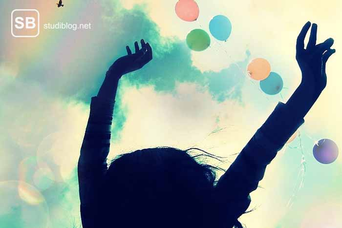 Studentin hält Hände in die Höhe, über ihr fliegen Luftballons zum Thema Stolpersteine überwinden