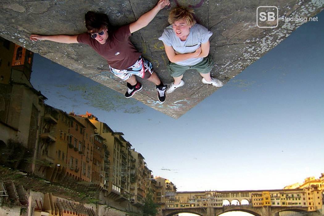 2 Jugendliche auf einer Reise die auf der Straße liegen - das Bild ist nach oben gespiegelt, so dass es aussieht, als würden die beiden an der Decke hängen.