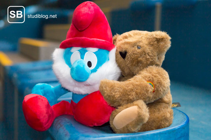 Papa Schlumpf schmust mit einem Bären in Form zweier Stofffiguren zum Thema Knick-Pimmel am Bonner Tatort