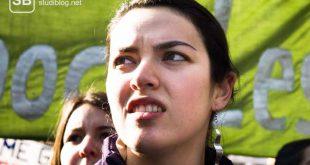 Studentin vor einem Demo-Banner zum Thema Streik der Studenten für besser Studienbedingungen