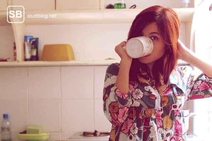Studentin steht alleine in der Küche mit einer Tasse Kaffee zum Thema allein und sturmfrei in der WG