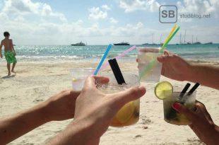 Studenten sitzen am Strand und spielen Trinkspiele