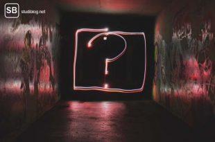 Die Frage was nach dem Abitur kommt - Leuchtendes Fragezeichen an einer dunklen Wand.