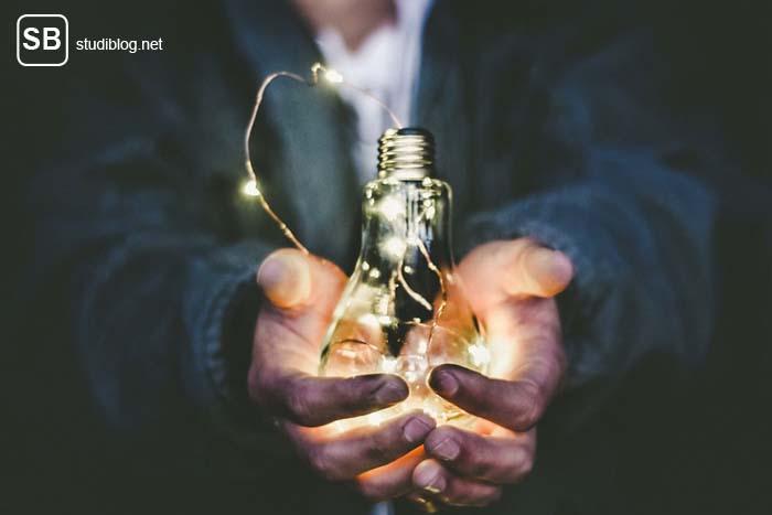 Mann hält eine leuchtende Glühbirne in den Händen - Warum eine Krisen keine Chance ist.