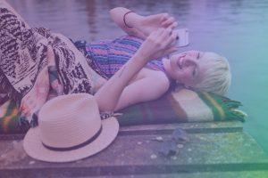 Junge Frau liegt neben einem Seeufer, wo sie sich mit dem Handy die Enpure App anschaut - dein neuer Stromtarif.