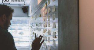 Ein junger Grüner steht vor einer Wand aus Post-its und geht die Themen durch - ein erfolgreiches Startup gründen.