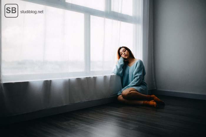 """Frau sitzt am Boden neben einem Fenster - Wie aus Britney Spears """"Hit me Baby one more time"""" emotionaler Missbrauch wurde."""