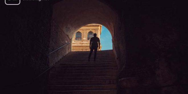 Mann geht eine Steintreppe hoch Richtung Tageslicht - kleine Schritte Lern-Strategie.