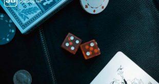 2 rote Würfel, 1 Poker-Chip und 1 Joker-Spielkarte liegen verstreut auf einem Tisch - Sportwetten Jobs, Chancen und Risiken.