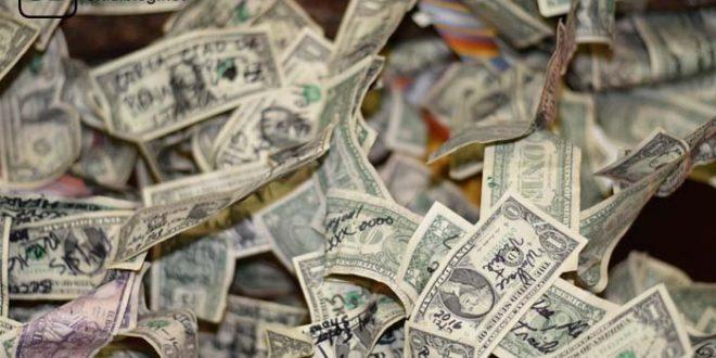 Teilweise mit schwarzem Stift beschriebene Dollarnoten liegen verstreut im Raum - Geld anlegen beim Wertpapierhändler in Deutschland.