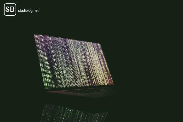 Virtual Uni - Im Dunkeln steht ein aufgeklappter Laptop auf dem eine Codierung zu sehen ist.