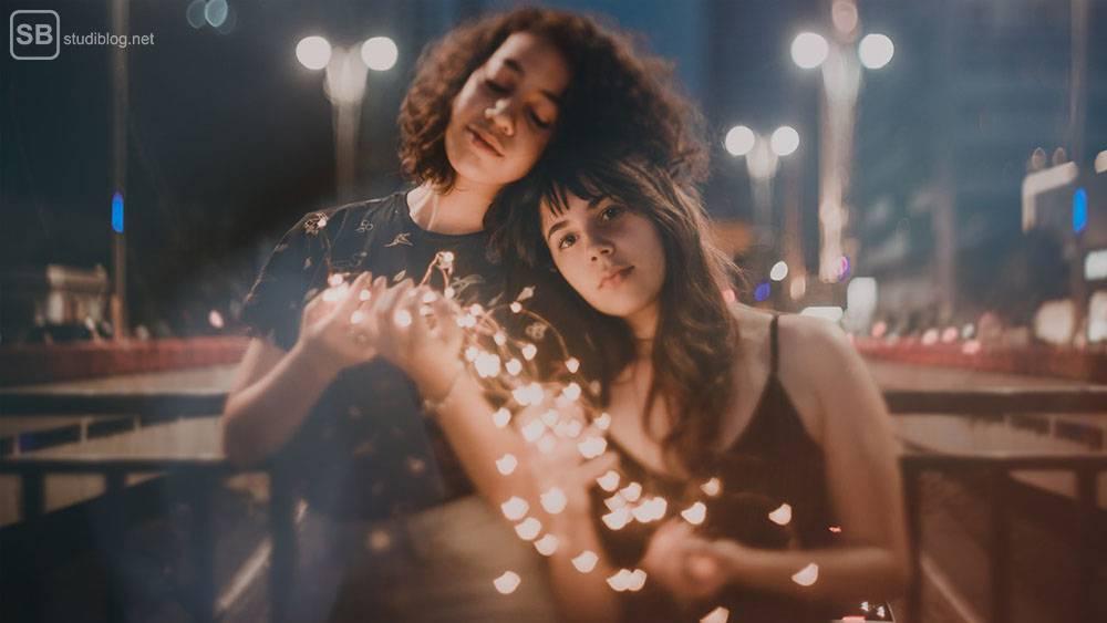 Freundschaften in den Zwanzigern: Zwei Freundinnen stehen in der Nacht mit einer Lichterkette in der Hand