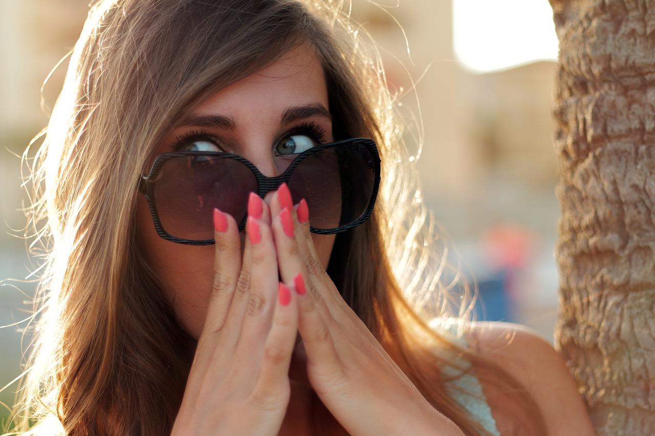 Frau hält die Hände vor Empörung vor den Mund wegen Dick Pics.