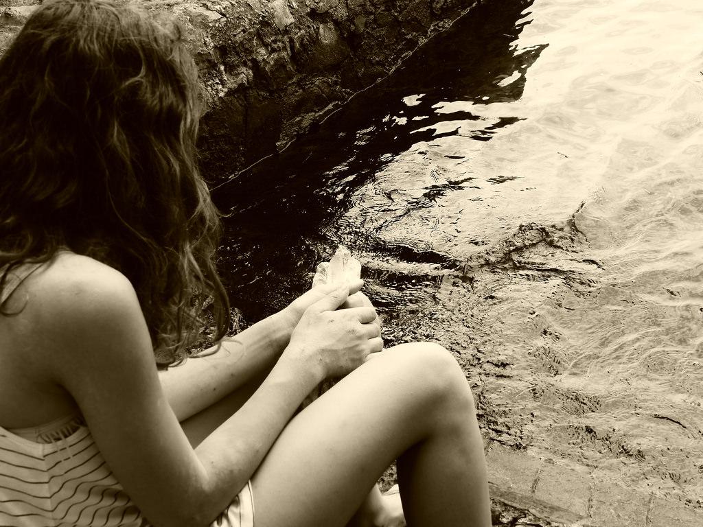 Eine Frau sitzt einsam an einem Seeufer ohne ihre beste Freundin.