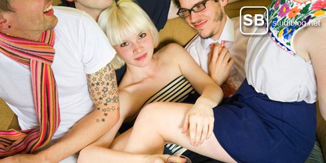 Bild einer Party mit Studenten, die übereinander auf einer Couch liegen
