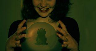 Ein Mädchen lässt eine Kugel zwischen ihren Händen schweben in der der Frosch aus dem Märchen des Froschkönigs sitzt.