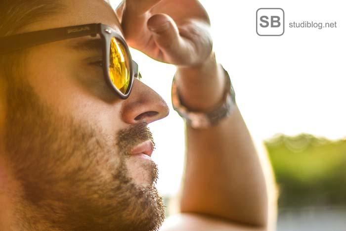 Ein Student sitzt mit Sonnenbrille lässig in seinem Wagen zum Thema Luxus im Studium - warum ein Luxusstudent 1500 Euro im Monat braucht
