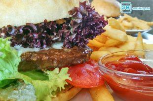 Selbstgemachter Burger mit Pommes, Salat, Tomaten, Gurken und Ketchup.