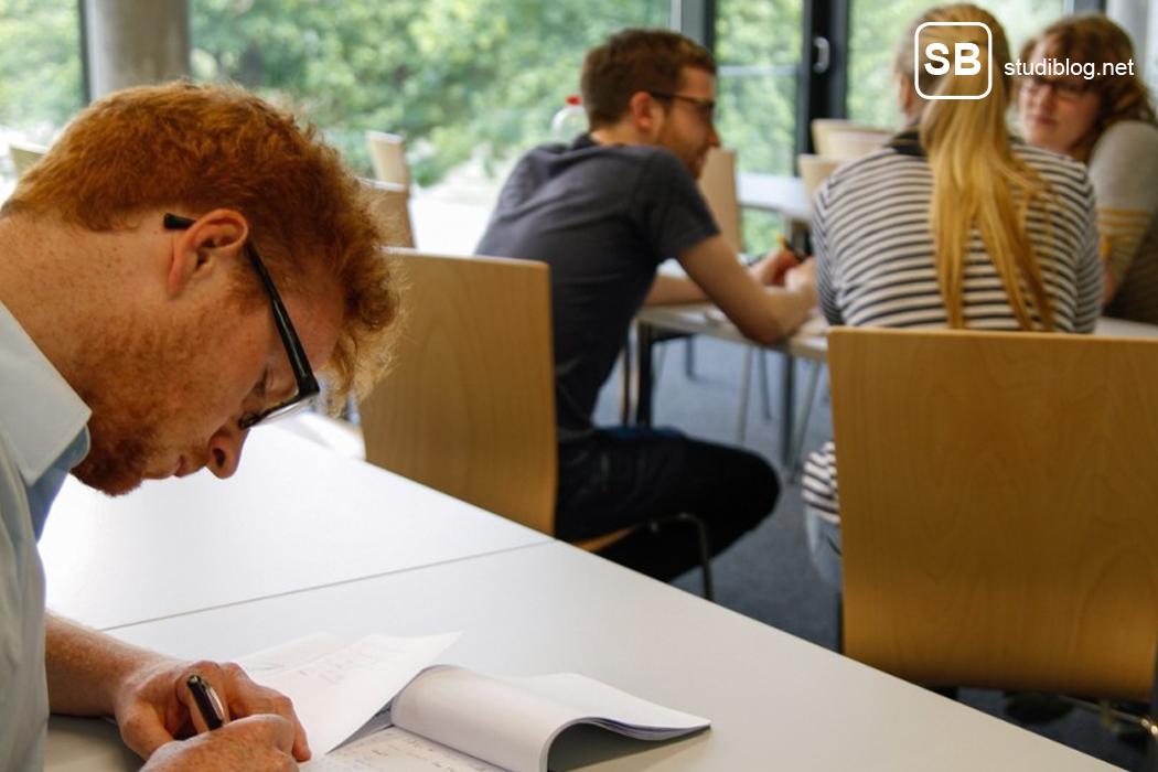 Student übt sich in der Selbstmotivation während mehrere Studenten gegenüber eine Lerngruppe bilden für die Klausurvorbereitung.