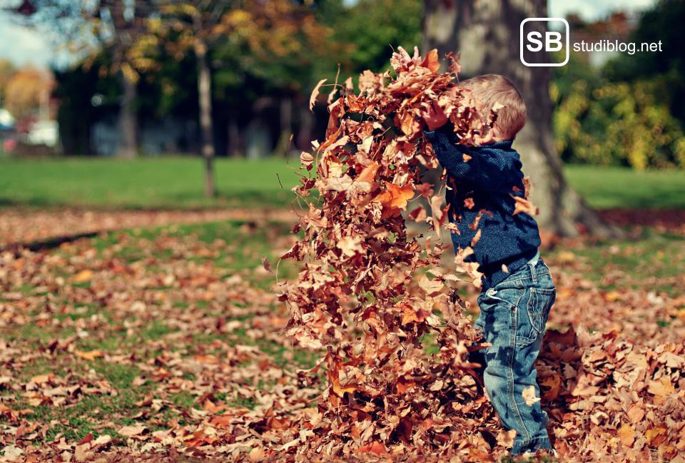 Ein Kind, das Blätter in die Luft wirft -Gegenteil zum erwachsen werden