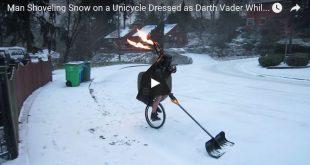 Vorschaubild auf dem ein Mann auf einem Einrad in einem Darth-Vader-Kostüm und einem brennenden Dudelsack eine Schneeschaufel vor sich her schiebt