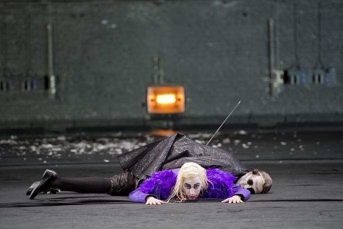 Bild aus der Oper: Don Giovanni liegt auf dem Bauch mit Blick Richtung Betrachter und auf ihm der tote Komtur.