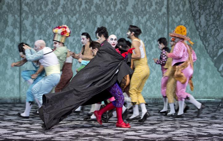 Bild aus der Oper: Don Giovanni läuft im Vordergrund nach rechts und einige Chorsolisten dahinter nach links.