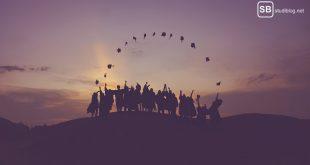 Promotion im Ausland: Mehrere promovierte Studenten werfen vorm Sonnenuntergang ihre Doktorhüte in die Luft