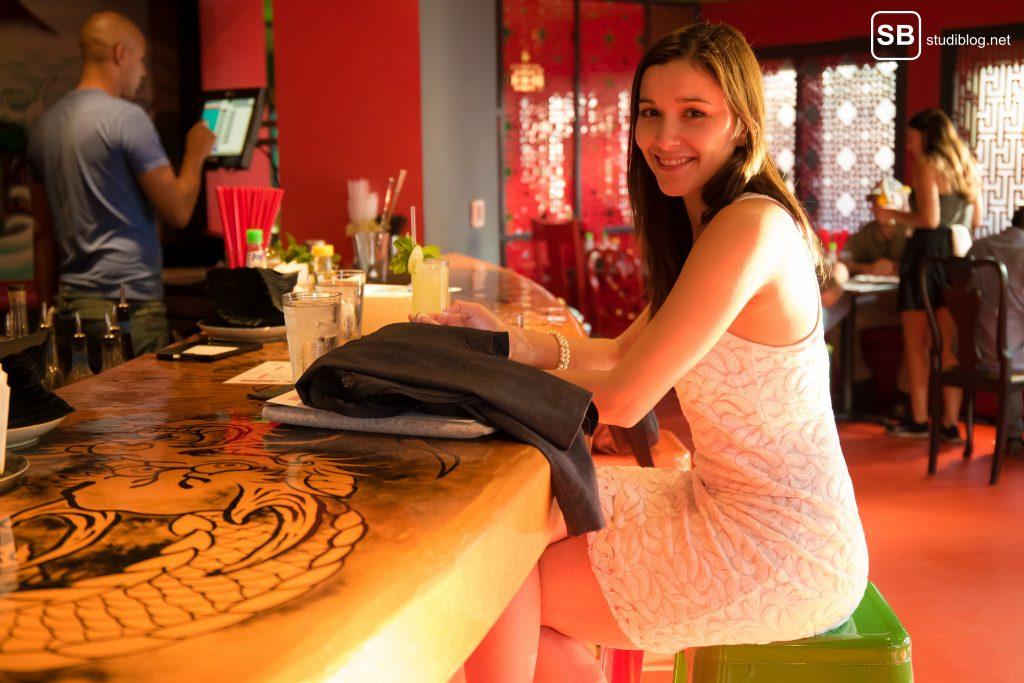 Katastrophen beim Date: Frau wartet im weißen Kleid am Tresen einer Bar.
