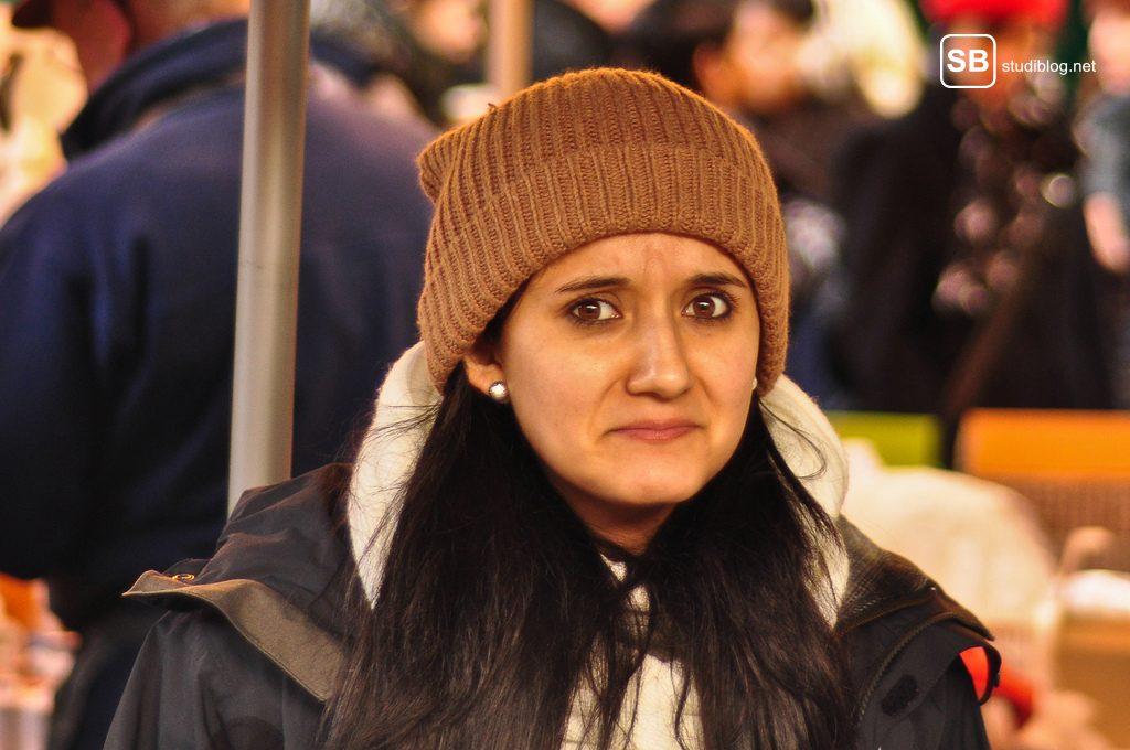 Katastrophen beim Date: Frau mit Beanie schaut belustigt und zugleich stirnrunzelnd in Kamera.