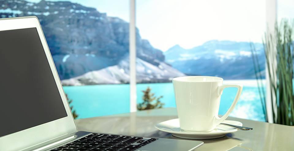 Praktikant - Do's und Don'ts: Laptop und Tasse vor Aussicht auf Berge und einen See