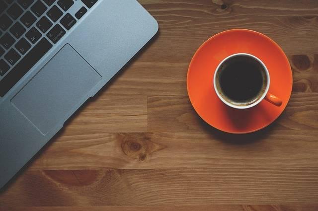 Das Leben wenn du selbstständig bist: Eine Tasse Kaffee steht neben einem Laptop