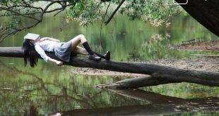 Artikelbild zum Thema Knappheit des Wohnraums für Studierende in Deutschland. Gezeigt wird ein schlafendes Mädchen auf einem Baumstamm mit einem Buch auf dem Gesicht an einem Flussufer