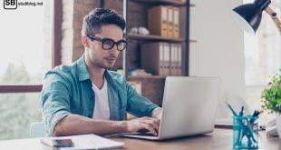 Selbstständigkeit nach dem Studium: Junger Mann im Hemd sitzt am Schreibtisch an seinem Laptop