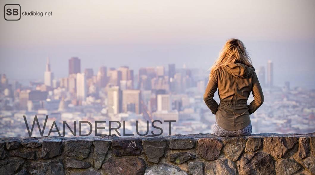 Mädchen sitzt auf einer Mauer vor der Skyline einer Stadt. Neben ihr steht Wanderlust