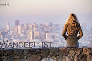 Wanderlust: A girl sitting on a wall infront of a city skyline