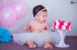 Baby sitzt in einem Röckchen neben einer Torte und Luftballons