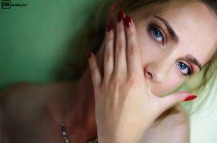 Leere spüren: Junge Frau mit roten Fingernägeln, die sie sich vor's Gesicht hält