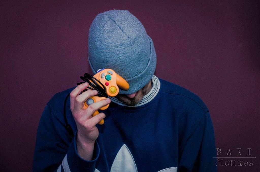 Single Klischees: Junger Mann hält sich einen Controller vor's Gesicht