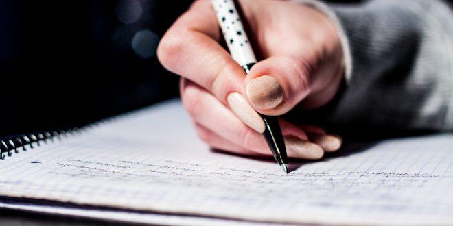 Nahaufnahme einer Frauenhand, die am Prüfungstag eine Prüfung schreibt