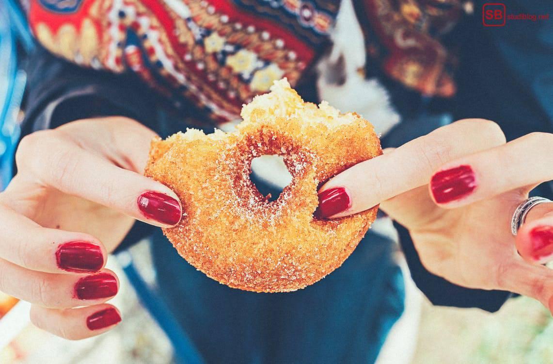 Unvernunft und Leichtsinn: Ein Mädchen mit roten Nägeln hält einen Donut vor sich.