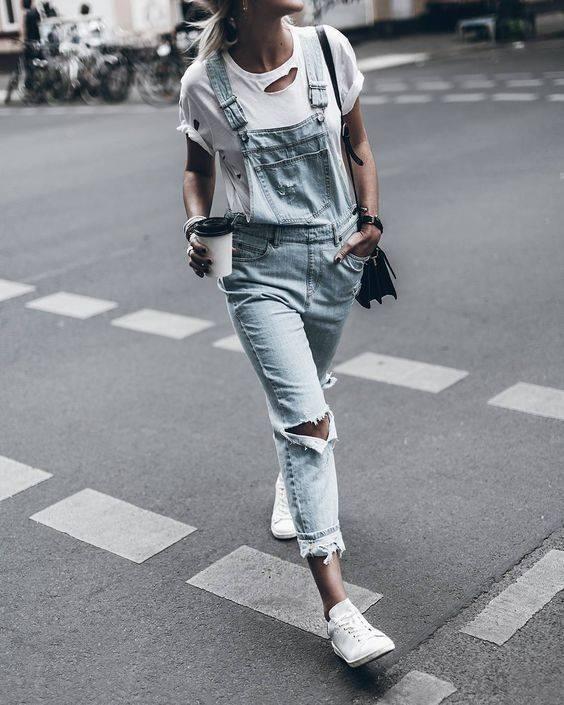 Trend der 90er: Frau läuft über die Straße in Jeans-Latzhosen
