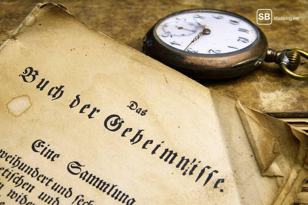 Antikes Buch mit aufgeschlagenem Deckel und daneben einer alten Taschenuhr - Der Langzeitstudent am Campus.