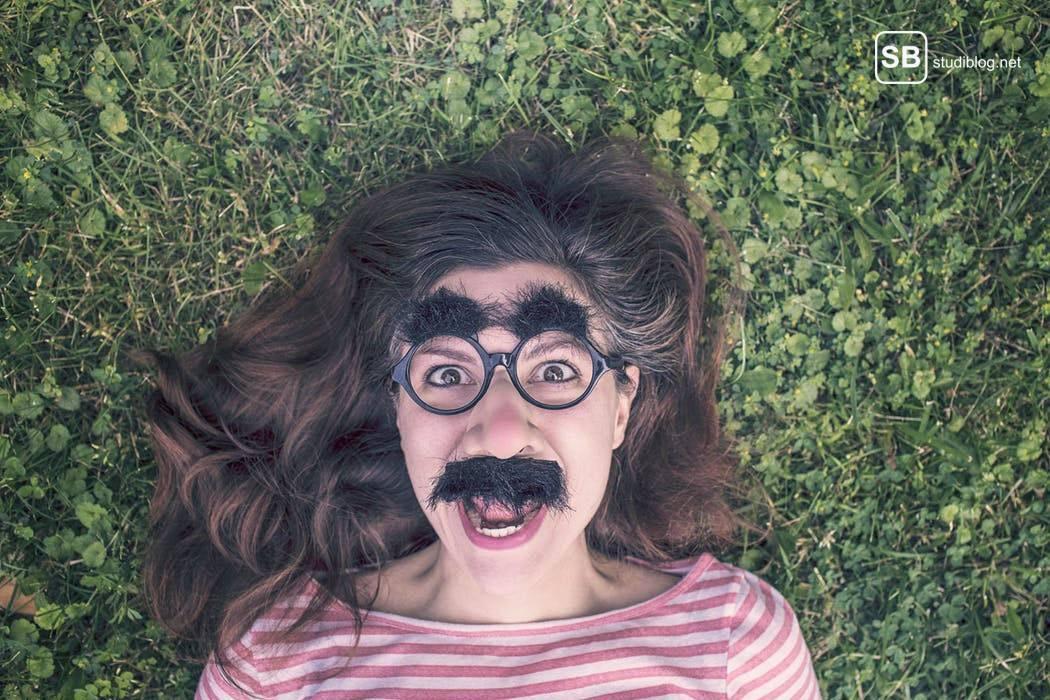 Brünette Frau liegt mit aufgeklebten Augenbrauen und Bart in einer Wiese - Der Psychologiestudent.