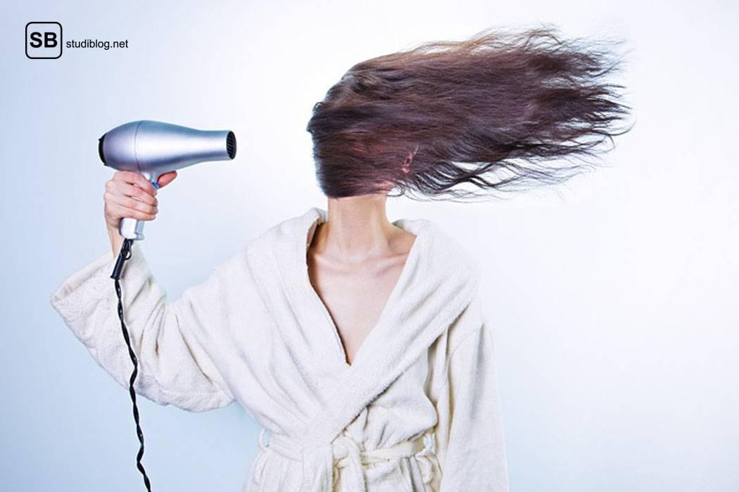 Frau steht im Bademantal mit Föhn in der Hand da und bläst sich die Haare quer übers Gesicht - total erwachsen eben.