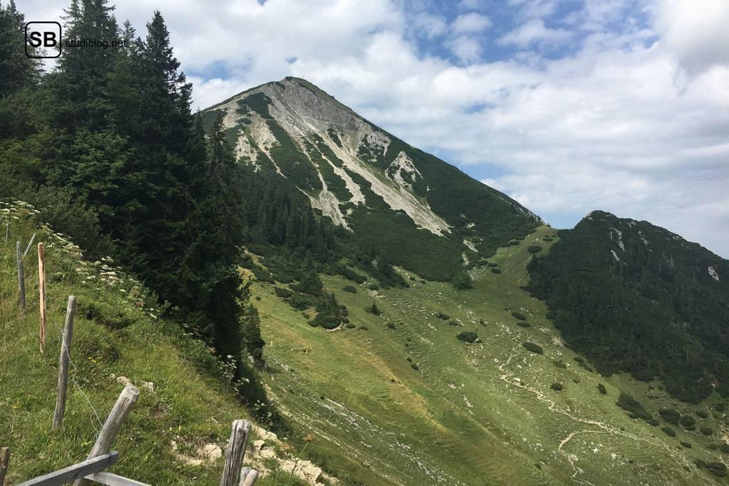 Wochenende auf der Alm: Blick auf das Gipfelkreuz von einem Wanderweg aus - Geigelstein.