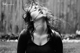 Dunkelhaarige Frau wirft ihren Kopf zurück mit vom Sommerregen nassen Haaren.